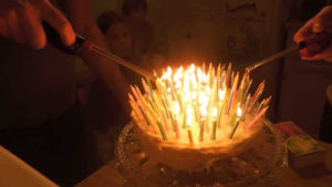 Two people lighting cake with many candles